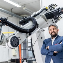 Jun. Prof. Andreas Wortmann vor einem Roboter am Institut für Steuerungstechnik der Werkzeugmaschinen und Fertigungseinrichtungen (ISW). Universität Stuttgart / Uli Regenscheit