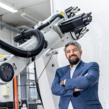 Jun. Prof. Andreas Wortmann vor einem Roboter am Institut für Steuerungstechnik der Werkzeugmaschinen und Fertigungseinrichtungen (ISW).